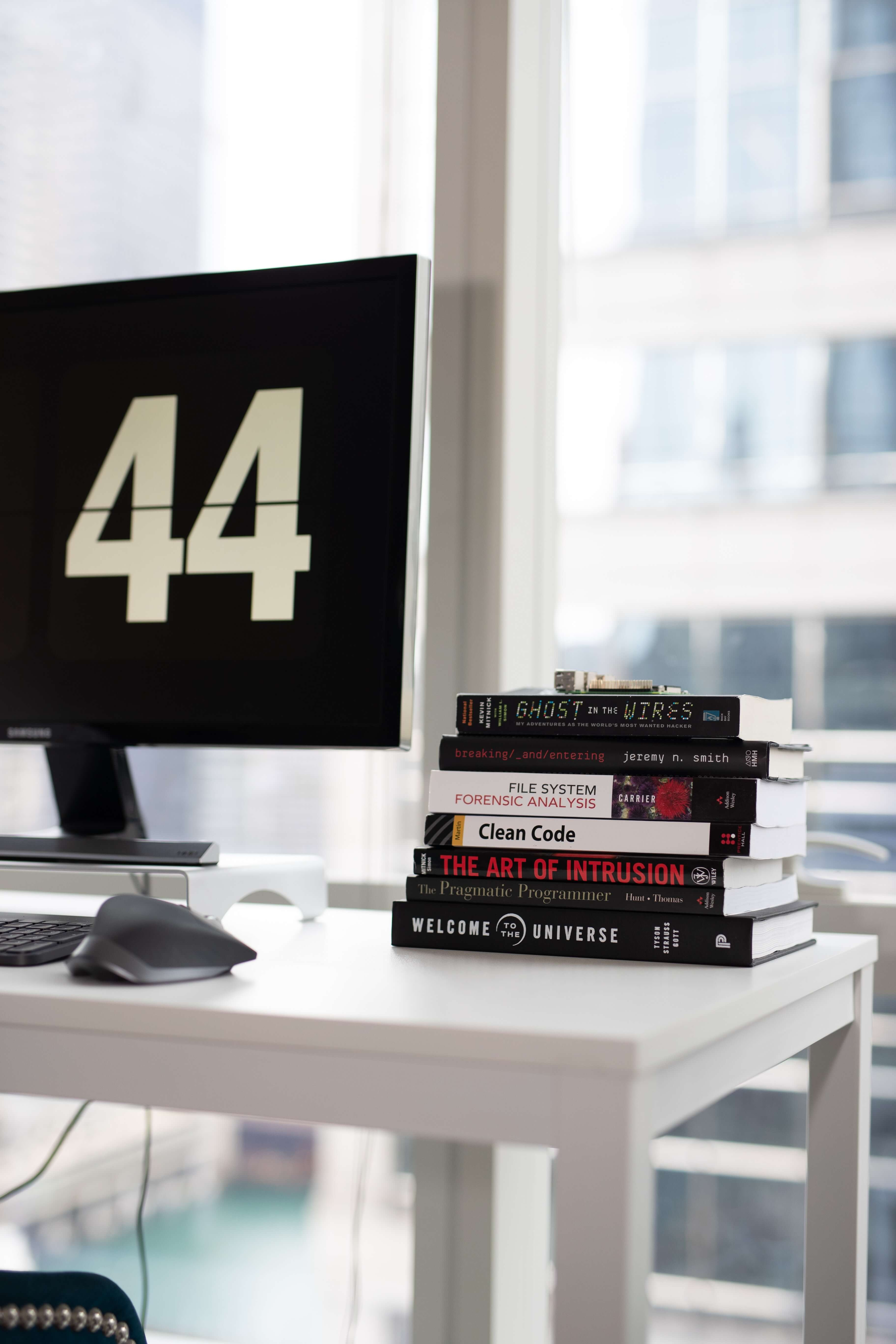 stack of books next to a computer